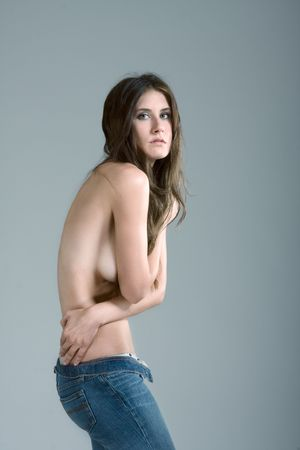 Topless female fashion model with long hair covering her breast in blue jeans Stock Photo - 5577364
