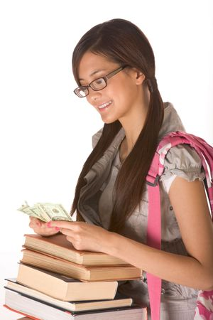 Asian young woman college student with backpack in eyeglasses and pile of books counting money  photo