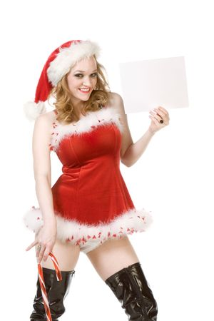 Blond sensual pinup woman in Christmas Mrs Santa Claus outfit and black thigh high leather boots holding sheet of white paper. Can be used as greeting card or your text or additional graphics can be added according to needs photo