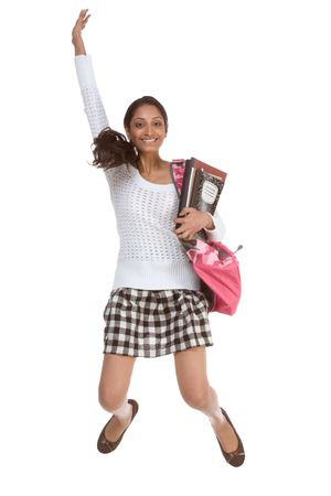 brunnett: education back to school series - Friendly ethnic Indian woman high school student with backpack and composition book in checkered uniform skirt jumping in excitement