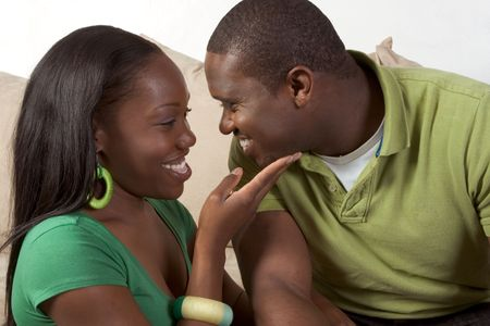 Young African American couple sitting in living room on couch enjoying time together