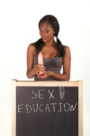sex education: Young ethnic black African-American female college student by school chalkboard teaching and explaining proper usage of condom use vibrator instead of penis. Can be used as template for sex education themed posters Stock Photo