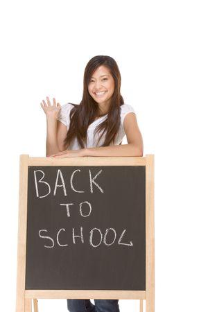 Friendly Asian High school girl student standing in jeans by blackboard that has text Back To School written by chalk