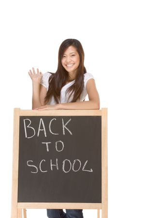 Friendly Asian High school girl student standing in jeans by blackboard that has text Back To School written by chalk photo