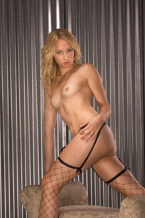 Naked woman in fishnet stockings and garter belt standing by small couch in seductive provocative pose photo
