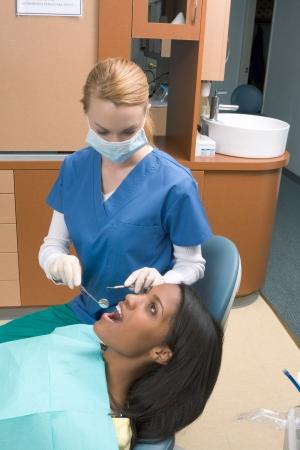 젊은 백인 흑인 인종 흑인 여성 백인 라텍스 장갑 및 마스크 금발의 백인 치과 의사가 그녀의 치아의 상태를 확인하면서 입을 열고 스톡 콘텐츠