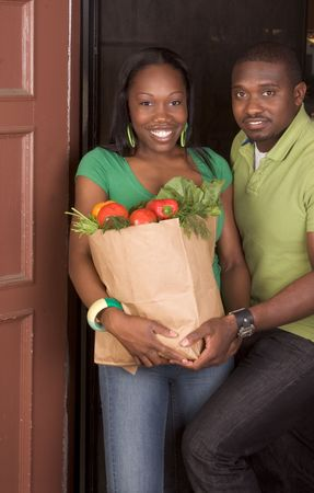 Young ethnic African American couple coming back home, returning from store with paper bag full of vegetables Banque d'images