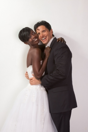 interracial marriage: smiling laughing newlywed young ethnic black African American woman and mid aged Caucasian man