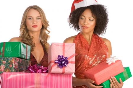 두 여자 한 백인 및 두 번째 민족 라티 나 부인 산타 클로스 모자 휴가의 스택과 함께 제공합니다. 금발 모델은 훨씬 더 큰 말뚝을 가지고 있으며 히스패닉계 여성은 부끄럽고 부끄럽지 않습니다.