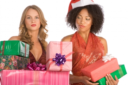 brunnet: Two females one Caucasian and second ethnic Latina in Mrs. Santa Claus hat with stack of holiday presents. Blond model has much bigger pile and Hispanic lady enviously and disapprovingly looks on it.