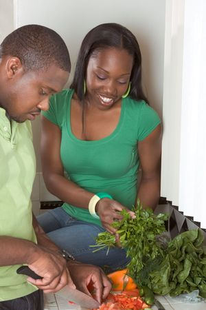 Young black African American couple preparing vegetable salad on kitchen countertop photo