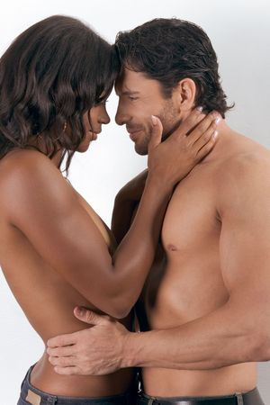 Loving affectionate nude interracial heterosexual couple in affectionate sensual kiss. Mid adult Caucasian men in late 30s and young mulatto biracial female mix of black African American, Native American and German ethnicity in 20s Stock Photo