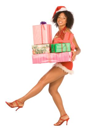 Dark skinned middle aged woman in sexy Mrs. Santa Claus outfit holding stack of gift boxes wrapped in paper and decorated by bows