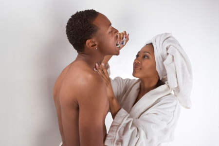 Ethnic sensual couple, African American man and woman of Creole ethnicity male wrapped in bathtowel and female in white bathrobe brushing teeth of her boyfriend photo