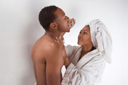 bathrobes: Pareja �tnicas sensual, afroamericano y una mujer de la etnia creole hombres envueltos en bathtowel y mujeres en bata blanca a cepillar los dientes de su novio Foto de archivo