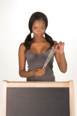 sex education: Young ethnic black female college student with condom by school chalkboard. Can be used as template for sex education themed posters or invitations