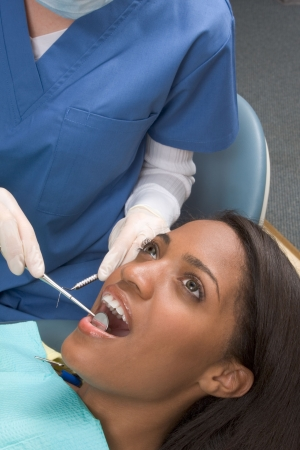 african ethnicity: Young African-American ethnic black female opening her mouth while dentist in white latex gloves check condition of her teeth