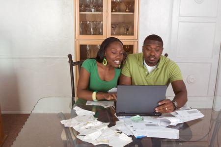 Financieel adviseur te helpen organiseren en optimaliseren van huis financiën rekeningen, jonge zwarte Afrikaanse Amerikaanse paar zitten door glazen tafel met draag bare pc, laptop en probeert te werken door middel van de stapel van de rekeningen te betalen ze on-line