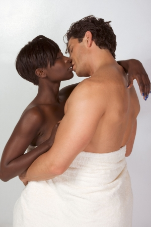 sensual young ethnic black African American woman and mid aged Caucasian man in love hugging wrapped in bathtowel
