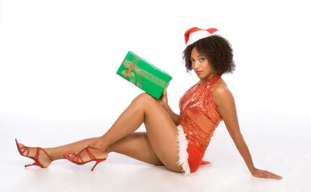 Sexy female in Christmas outfit sitting on floor and holding big Christmas gift box photo