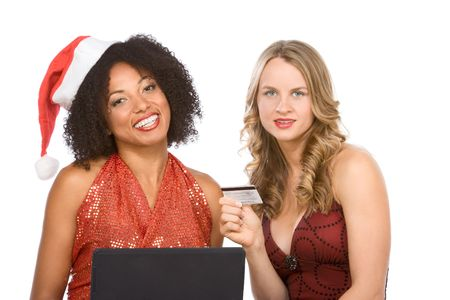 Two attractive females (one ethnic in sexy Mrs. Santa Claus costume and one Caucasian blonde in red dress) browsing internet on notebook portable computer, while holding credit card in hand  Imagens