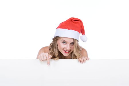 Template - Sexy blonde young woman in Mrs Santa Claus hat holding a sign with copyspace. Isolated on white. Extra white space with your message can be added to the bottom of the picture photo