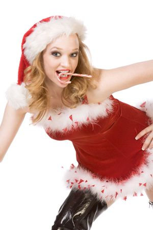 Blond excited pinup dancing woman in Christmas outfit and thigh high black leather boots holding candy cane stick photo