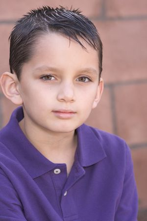 Headshot of elementary age kid in short sleeve polo shirt. Multi-ethnic of Caucasian and Hispanic (Mexican) mix