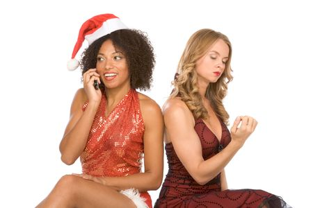 Two lesbian friendly lovers female one Caucasian and second ethnic Latina in Mrs. Santa Claus. Hispanic lady talking on mobile phone