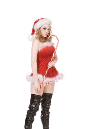 Blond excited pinup dancing woman in Christmas outfit and thigh high black leather boots holding huge candy cane stick photo