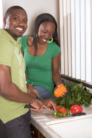 domestic kitchen: Young black African American couple preparing vegetable salad on kitchen countertop