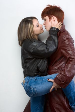 Kiss and hugging of two young lesbian women Latina of Puerto Rican Ethnicity and red head Caucasian engaged playing in loving sexual games
