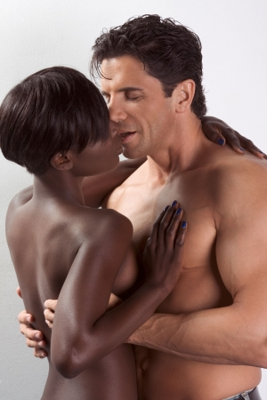 Loving affectionate nude heterosexual couple in sensual kiss and hug. Mid adult Caucasian men in late 30s and young black African-American woman in 20s Stock Photo - 6025236