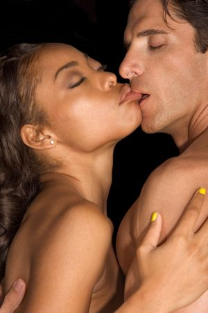 Loving affectionate nude interracial heterosexual couple in affectionate sensual kiss. Mid adult Caucasian men in late 30s and young black African-American woman in 20s photo