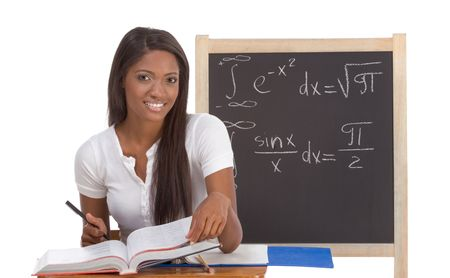 formals: High school or college ethnic African-American female student sitting by the desk at math class. Blackboard with advanced mathematical formals is visible in background