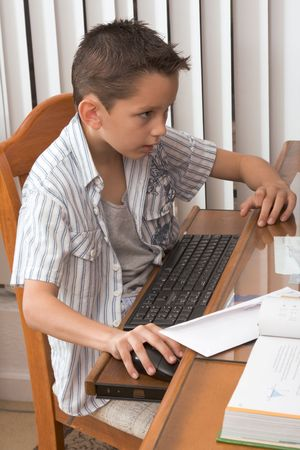 Young Multi-ethnic of Caucasian and Hispanic (Mexican) mix boy engaged in PC computer activity