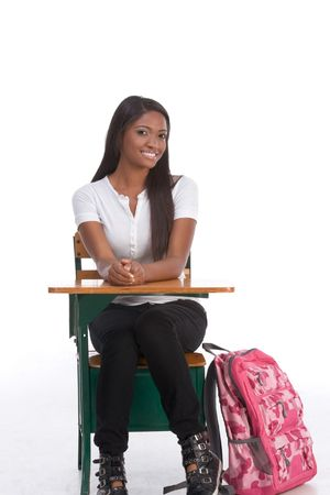 brunnet: education series - Friendly ethnic black woman high school student sitting by school desk with pink backpack by her legs