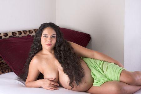 seminude: gravidanza 3 settimane prima del parto. Seminuda etnica Hispanic Latina donna con i capelli lunghi, sdraiata sul letto