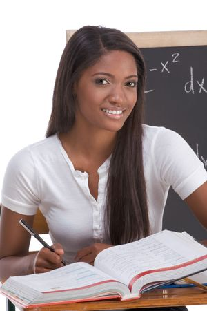 High school or college ethnic African-American female student sitting by the desk at math class. Blackboard with advanced mathematical formals is visible in background photo