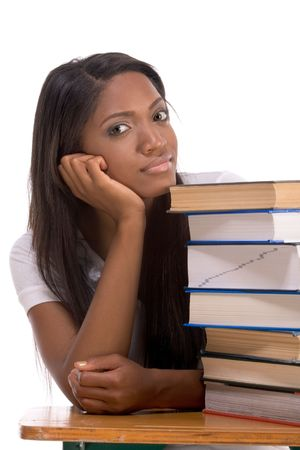 High school or college ethnic African-American female student sitting by the desk with lot of books in class or library photo