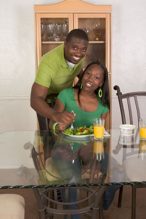 Young black African American couple sitting by glass table and eating meal of salad, bagels with cream cheese and orange juice photo