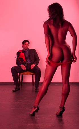 Ethnic black striptease exotic dancer performing for middle aged Caucasian man in business suite sitting on chair photo