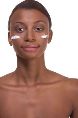 Skincare - Young naked ethnic African-American woman with slicked back hair applying cream moisturizer on her face after sauna photo