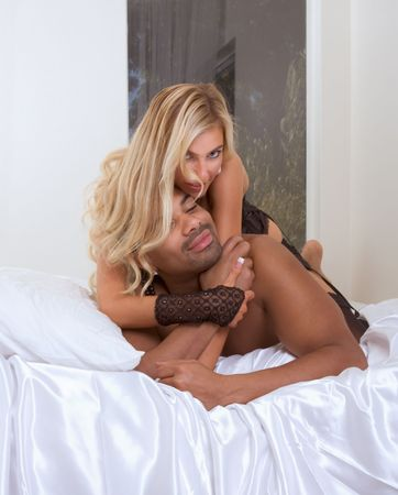 adult sex: Playful sensual heterosexual couple - Caucasian woman and ethnic black man of mixed African-American and Italian ethnicity Stock Photo