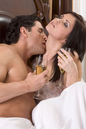 adult sex: Young sexy heterosexual couple celebrating with wine in bed Stock Photo