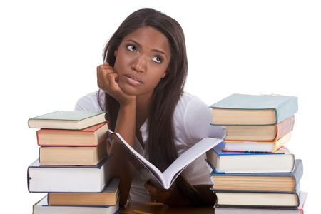 bore: igh school or college ethnic African-American female student sitting by the desk with lot of books in class or library and doing homework