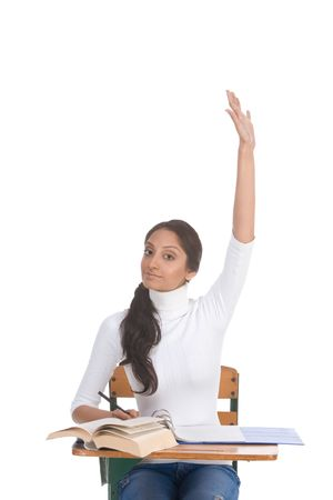 age 16 17 years: High school or college female student sitting by the desk raising her arm signaling that she know and is ready to answer