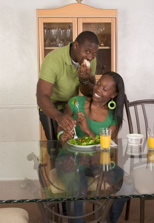 red skinned: Young black African American couple sitting by glass table and eating meal of salad, bagels with cream cheese and orange juice