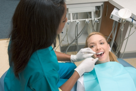 brunnett: Young blond Caucasian female opening her mouth while African-American ethnic dentist in white latex gloves check condition of her teeth