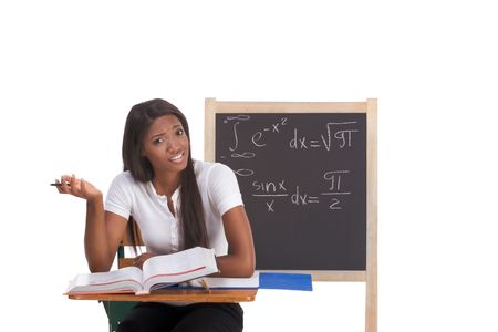 formals: Stressed High school or college ethnic African-American female student sitting by the desk at math class. Blackboard with complicated advanced mathematical formals is visible in background